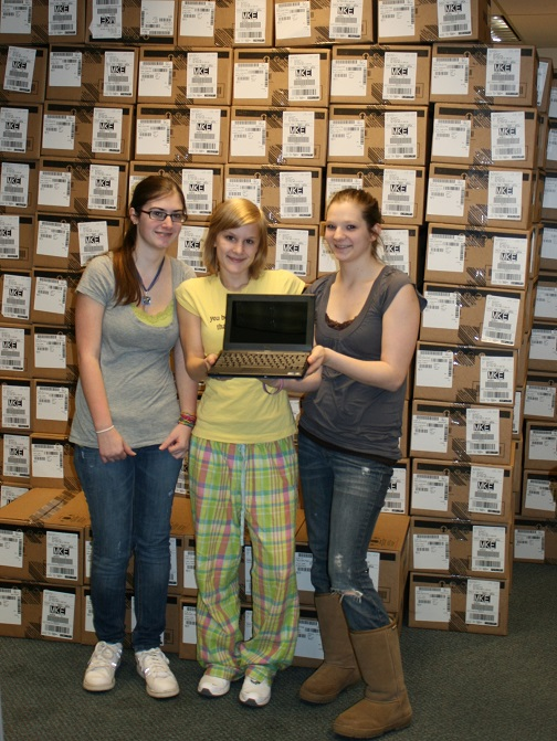 Sault High students Deveney Zabelka, Mercedes Komarnizki, and Julia Hook check out the new netbook in front of a seemingly endless wall of boxes of netbooks.