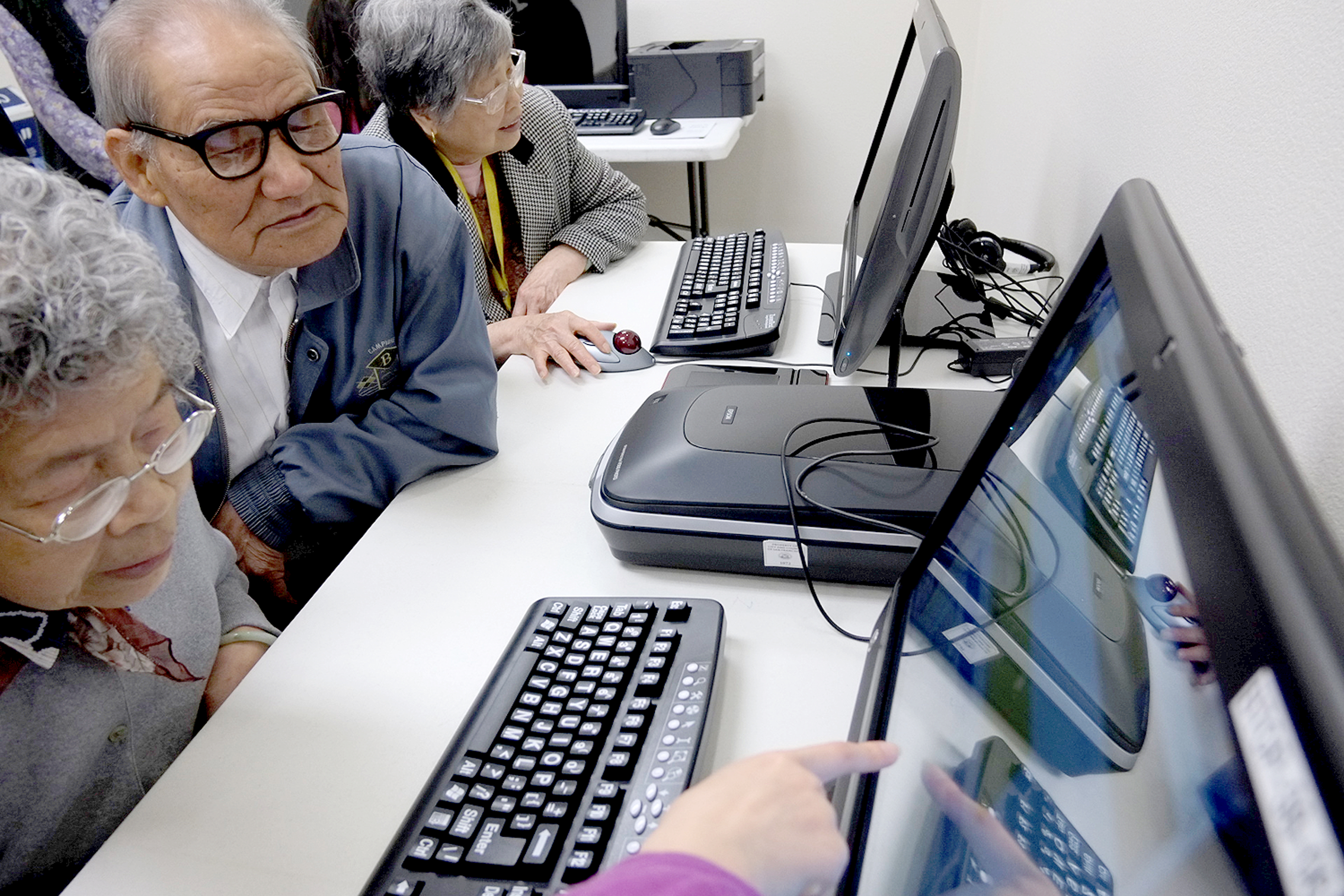 Older people working on a computer with help from an instructor